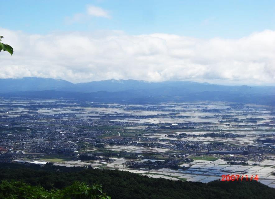 高田平野の田園地帯の先に東頸城丘陵
